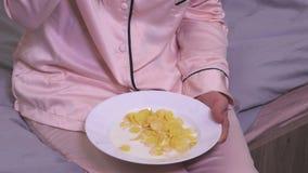 A mulher no pijama come flocos de milho com leite na cama vídeos de arquivo