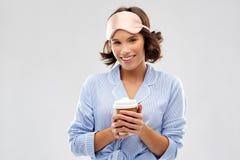 Mulher no pijama e m?scara do sono com copo de caf? imagem de stock royalty free