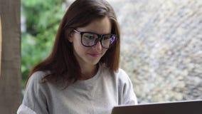 Mulher no portátil do uso dos vidros Mulher de negócios que trabalha no computador durante férias vídeos de arquivo