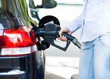 Mulher no posto de gasolina, enchendo-se acima de seu carro fotos de stock royalty free