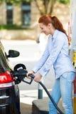 Mulher no posto de gasolina, enchendo-se acima de seu carro imagens de stock