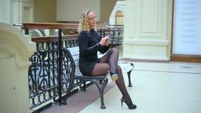 Mulher no preto com o telefone no banco video estoque