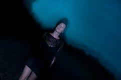 Mulher no preto encoberto na escuridão e no mistério Imagens de Stock