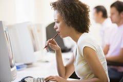 Mulher no quarto de computador que olha o monitor Imagem de Stock