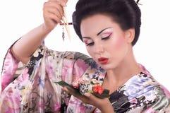 Mulher no quimono japonês com hashis e rolo de sushi Fotos de Stock Royalty Free