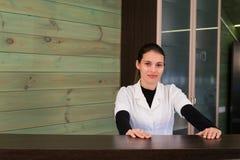 A mulher no receptrion sorri e dá boas-vindas ao visitante virtual em termas ou na clínica moderna Papéis com acordo em sua mão imagem de stock royalty free