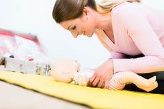 Mulher no renascimento praticando do curso dos primeiros socorros do infante no bebê d fotografia de stock royalty free