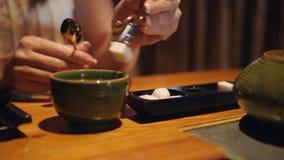 A mulher no restaurante põe-no em um copo do chá e em fatias de açúcar vídeos de arquivo