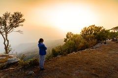 Mulher no revestimento azul que olha o por do sol no penhasco no inverno Imagens de Stock