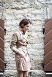 A mulher no revestimento bege com bolsa olhou para baixo Imagem de Stock Royalty Free