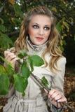 Mulher no revestimento bege perto da árvore Imagens de Stock Royalty Free