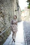 Mulher no revestimento bege perto da parede velha da cidade imagens de stock royalty free