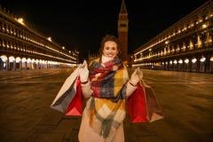 Mulher no revestimento do inverno que guarda sacos de compras na praça San Marco Fotografia de Stock Royalty Free