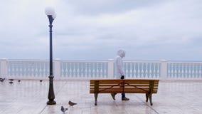 A mulher no revestimento e na capa brancos veio e sentou-se no banco no terraço bonito com opinião do mar na margem Vista traseir filme