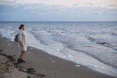 Mulher no revestimento que anda no litoral imagem de stock