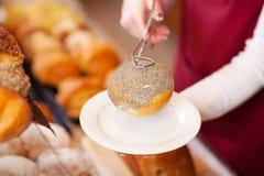 Mulher no rolo de pão do serviço da padaria Foto de Stock Royalty Free