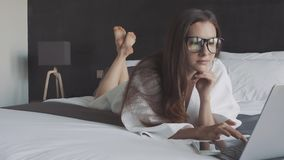 Mulher no roupão e no portátil brancos do funcionamento de vidros, mentira na cama Smartphone no computador Negócio em linha vídeos de arquivo