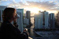 Mulher no roupão que bebe seu café ou chá da manhã em um balcão do centro Nascer do sol bonito em miami do centro Mulher que apre fotografia de stock royalty free