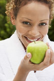 Mulher no roupão que guarda Apple verde fresco Fotografia de Stock Royalty Free