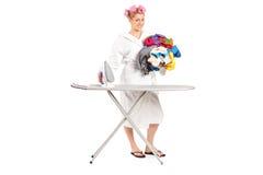 Mulher no roupão que prepara a roupa para passar Imagem de Stock Royalty Free