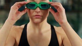 Mulher no roupa de banho que ajusta seus óculos de proteção video estoque