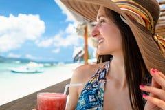 Mulher no roupa de banho que aprecia a bebida no café da praia no mar foto de stock royalty free