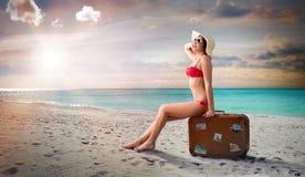 Mulher no roupa de banho que senta-se na mala de viagem em uma praia fotos de stock royalty free