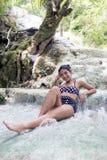 Mulher no roupa de banho retro que senta-se em uma cachoeira Fotografia de Stock Royalty Free