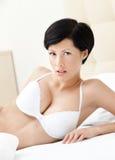 A mulher no roupa interior branco está encontrando-se na cama Imagens de Stock Royalty Free