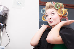 Mulher no salão de beleza, rolos louros dos encrespadores de cabelo da menina pelo cabeleireiro. Penteado. Imagem de Stock