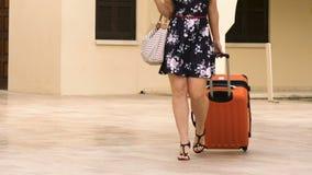 A mulher no salto alto calça o passeio com a mala de viagem rodada ao hotel, viagem de negócios vídeos de arquivo