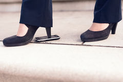 A mulher no salto preto calça a etapa no telefone Fotos de Stock