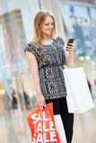 Mulher no shopping usando o telefone celular Foto de Stock Royalty Free