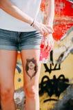 Mulher no short de calças de ganga com um copo de café cor-de-rosa fotos de stock royalty free