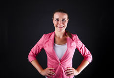 Mulher no siute cor-de-rosa sobre o sorriso escuro do fundo Foto de Stock Royalty Free