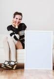 Mulher no sofá que guarda a placa da apresentação vazia Imagem de Stock Royalty Free