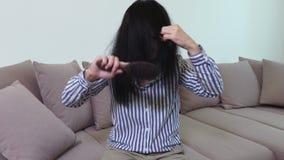 Mulher no sofá que penteia o cabelo filme