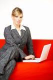 Mulher no sofá vermelho Imagens de Stock Royalty Free