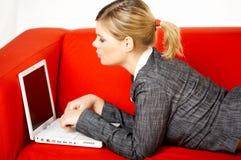 Mulher no sofá vermelho Imagem de Stock Royalty Free