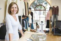 Mulher no sorriso da loja de roupa fotografia de stock