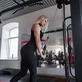 A mulher no sportswear preto está treinando no gym O conceito da beleza e da sa?de imagem de stock