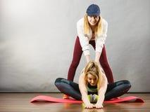 Mulher no sportswear que estica os pés com instrutor fotografia de stock royalty free