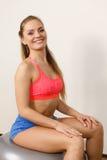 Mulher no sportswear que faz exercícios com bola do ajuste fotografia de stock