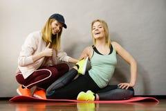 Mulher no sportswear que faz o exercício com instrutor fotografia de stock