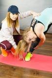 Mulher no sportswear que faz o exerc?cio com instrutor imagens de stock royalty free