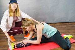Mulher no sportswear que faz o exerc?cio com instrutor imagem de stock