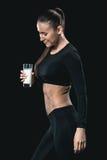 Mulher no sportswear que guarda o vidro do leite e que sorri, conceito vivo saudável imagens de stock