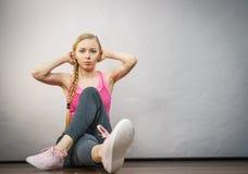 Mulher no sportswear que senta-se na terra imagem de stock royalty free