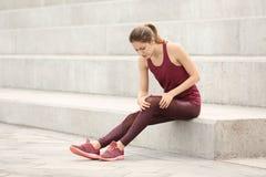 Mulher no sportswear que sofre da dor do joelho fotos de stock
