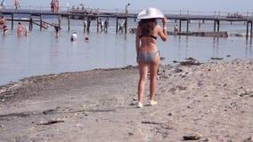 Mulher no sundress brancos que anda ao longo do litoral filme